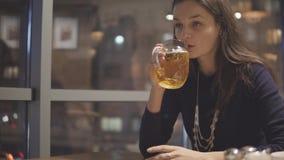 Ung kvinna som dricker öl i kafé lager videofilmer