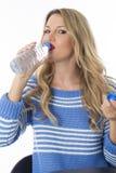 Ung kvinna som dricker från flaskan av mineralvatten Fotografering för Bildbyråer