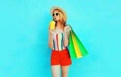 Ung kvinna som dricker fruktsaft som rymmer shoppa påsar i den färgrika t-skjortan, sommarsugrörhatt, solglasögon, röda kort royaltyfri foto