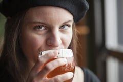 Ung kvinna som dricker Inda ljust öl Arkivbild