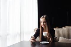 Ung kvinna som dricker kaffe i ett kafé och använder en mobiltelefon arkivbilder