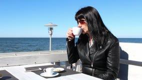 Ung kvinna som dricker kaffe i ett utomhus- kafé stock video