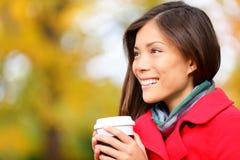 Ung kvinna som dricker kaffe i höst/nedgång Arkivfoto
