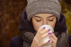 Ung kvinna som dricker kaffe i parkera arkivbilder