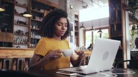 Ung kvinna som dricker kaffe, medan genom att använda bärbara datorn i kafé arkivfilmer