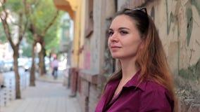 Ung kvinna som dricker kaffeanseende på gatan i stad stock video