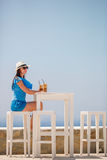 Ung kvinna som dricker kallt kaffe som tycker om havssikt Den härliga kvinnan kopplar av under exotisk semester på stranden som t Royaltyfria Foton