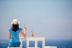 Ung kvinna som dricker kallt kaffe som tycker om havssikt Den härliga kvinnan kopplar av under exotisk semester på stranden som t Arkivbilder