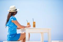 Ung kvinna som dricker kallt kaffe som tycker om havssikt Den härliga kvinnan kopplar av under exotisk semester på stranden som t Royaltyfri Foto