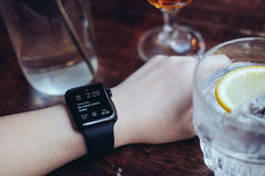 Ung kvinna som dricker med den smarta klockan på stången Arkivfoton