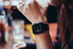 Ung kvinna som dricker med den smarta klockan på stången Royaltyfri Foto