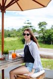 Ung kvinna som dricker morotsmoothien på den utomhus- stången Brunettflicka som tycker om i grön sikt och dricker fruktsaft på pa arkivbild