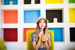 Ung kvinna som dricker orange fruktsaft i kafé varm sommar för dag Royaltyfria Bilder