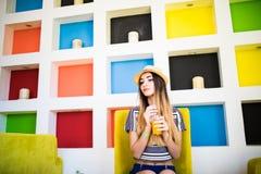 Ung kvinna som dricker orange fruktsaft i kafé varm sommar för dag Arkivbilder
