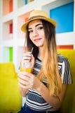 Ung kvinna som dricker orange fruktsaft i kafé varm sommar för dag Arkivfoto