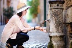 Ung kvinna som dricker rent vatten från springbrunnen i Rome, Italien arkivfoto