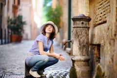 Ung kvinna som dricker rent vatten från springbrunnen i Rome, Italien royaltyfri foto
