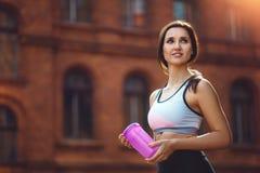 Ung kvinna som dricker sporttillägg, når att ha kört eller att ha övat som är utomhus- Fotografering för Bildbyråer