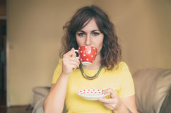 Ung kvinna som dricker te eller kaffe Royaltyfria Bilder