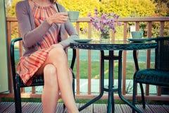 Ung kvinna som dricker te på farstubron Arkivbild