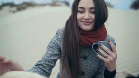 Ung kvinna som dricker varmt ånga te på stranden med hennes hund arkivfilmer
