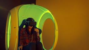 Ung kvinna som erfar virtuell verklighetsammanträde i växelverkande flyttningstol Arkivfoto