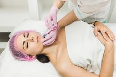Ung kvinna som får den kosmetiska injektionen i skönhetklinik arkivfoton
