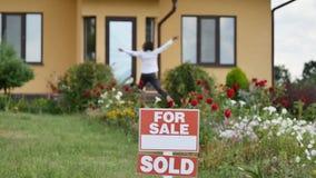 Ung kvinna som får en tangent till hennes nya hus från deras fastighetsmäklare på dörren av bakgrund för nytt hus Royaltyfri Foto