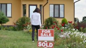 Ung kvinna som får en tangent till hennes nya hus från deras fastighetsmäklare på dörren av bakgrund för nytt hus Royaltyfri Bild