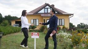 Ung kvinna som får en tangent till hennes nya hus från hennes fastighetsmäklare på dörren av bakgrund för nytt hus Royaltyfria Foton