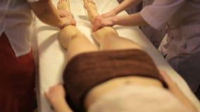 Ung kvinna som får fotmassage i den vård- brunnsorten Magi av nöje - Ayurvedic massage i sex händer lager videofilmer
