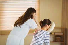 Ung kvinna som får massage i stol arkivbild