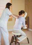 Ung kvinna som får massage i stol royaltyfri foto