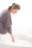 Ung kvinna som förbereder badkaret Royaltyfria Foton