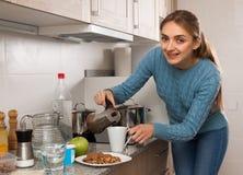 Ung kvinna som förbereder kaffe i köket fotografering för bildbyråer
