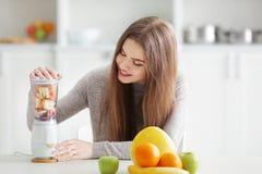Ung kvinna som förbereder nya smoothies i blandare arkivbilder