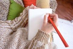 Ung kvinna som förbereder sig att skriva ett brev till jultomten arkivbild