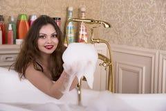 Ung kvinna som förbereder sig att ta ett bad Arkivfoton