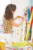 Ung kvinna som förbereder sig för easter. bakre sikt Fotografering för Bildbyråer