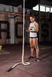 Ung kvinna som förbereder sig för repklättringövningen i idrottshall Arkivbilder