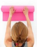 Ung kvinna som förbereder sig för yoga Arkivfoto