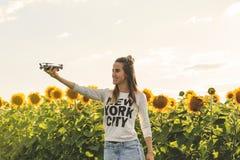 Ung kvinna som förestående rymmer att flyga det mini- surret utomhus Arkivbilder