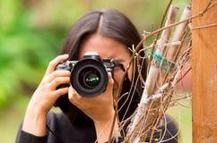 Ung kvinna som förföljer och tar bilder med hennes kamera, på yttersidan arkivbilder