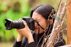 Ung kvinna som förföljer och tar bilder med hennes kamera, på yttersidan royaltyfri bild