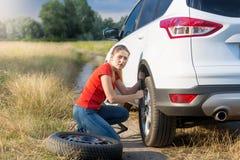 Ung kvinna som försöker att ändra det plana däcket och skruva av muttrar för bilhjul Royaltyfria Foton