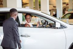 Ung kvinna som förvånas av den nya bilen, gåva för min härliga fru Arkivbilder