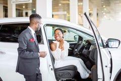Ung kvinna som förvånas av den nya bilen, gåva för min härliga fru Royaltyfria Foton