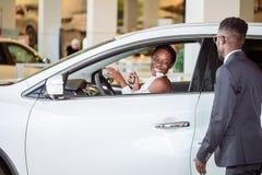 Ung kvinna som förvånas av den nya bilen, gåva för min härliga fru Royaltyfria Bilder
