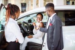 Ung kvinna som förvånas av den nya bilen, gåva för min härliga fru Royaltyfri Fotografi