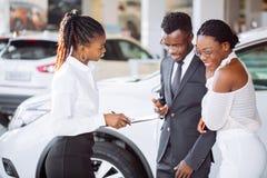 Ung kvinna som förvånas av den nya bilen, gåva för min härliga fru Arkivfoto